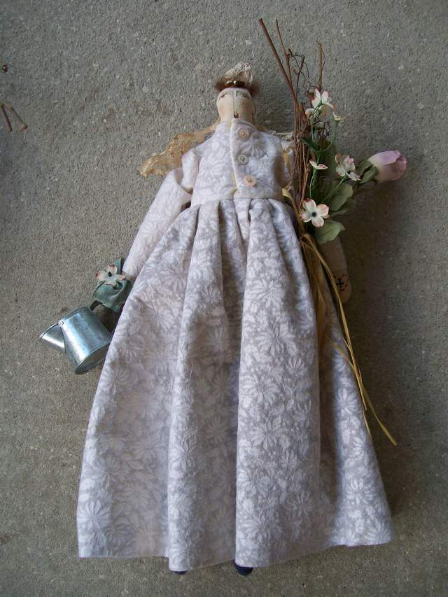 stuffed cloth doll, holding flowers, watering can