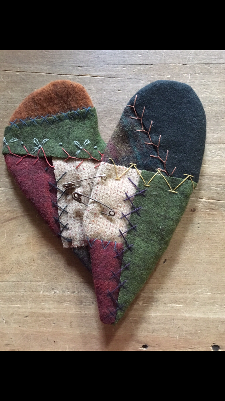 a pieced wool heart with decorative stitches