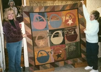 "Andrea Reynolds(l) and Lucille Kinzie, friends of Cheryle Harte's from California, are holding up Cheryle's ""Slim Pickins"" for us to enjoy. You can see the back of this quilt posted on the Back Porch Page........great job Cheryle, I love it."