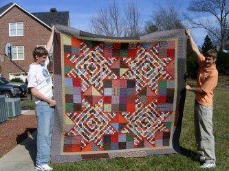 Debbie Carlton from Hickory, North Carolina just sent me this exciting picture of her Moonshine Quilt. Piecing 4 of the Moonshine blocks together, she made this wonderful bed quilt. Holding the quilt are her two sons, Troy on the left, Wade on the right.