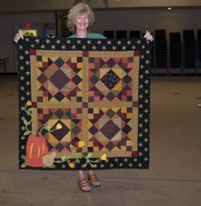 Donna O'Brien from California was in a class I taught - Primitive Sketches - at the Primitives of the Midwest a few years ago...it originally was a 3 block table runner but Donna decided to make 4 and make her's a wall hanging with fun applique down in th