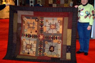 Lisa Johnson, the owner of the Picket Fence Quilt Shop in Wichita, Ks. brought her Bundling Board Quilt all the way to quilt market this fall to show me. I was so excited about what she made that both my pictures I took are quite lacking. What a beautiful